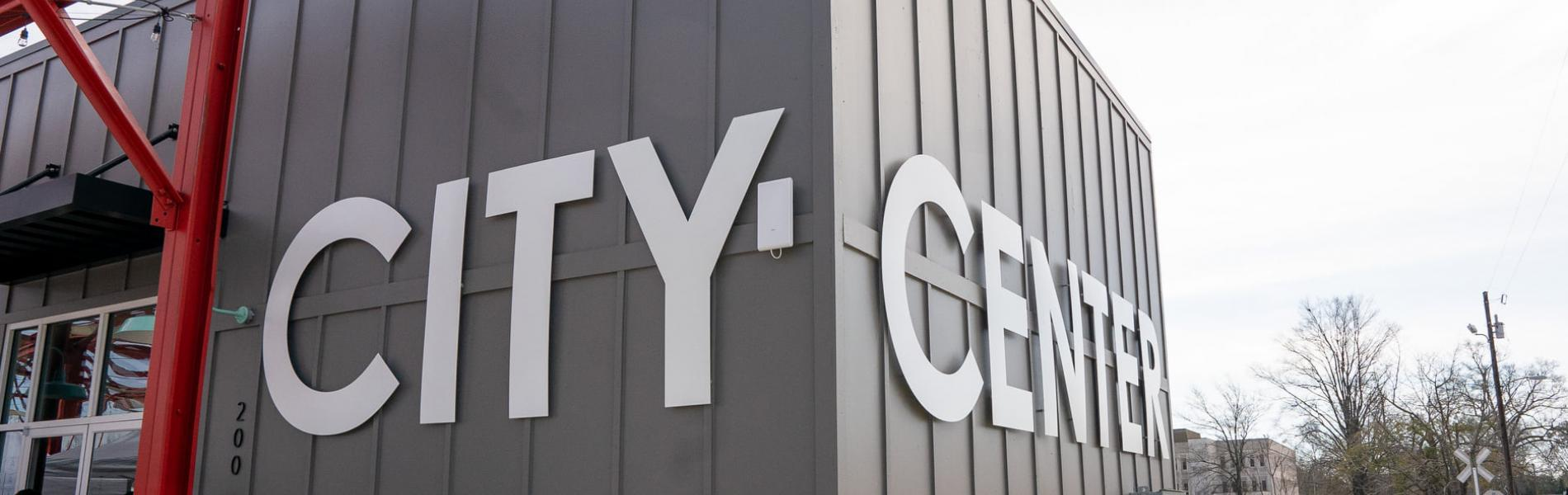 Grey building with the words City Center on the sides in large, white letters.